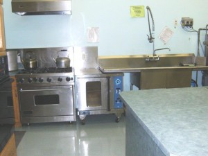 Industrial stove and sink in government inspected licensed kitchen